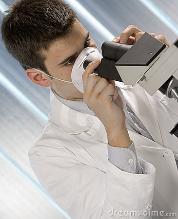 Young scientist watching inside microscope