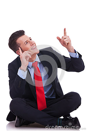 Young seated business man pointing