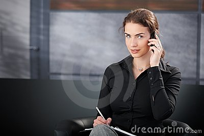 Young secretary talking on cellphone smiling