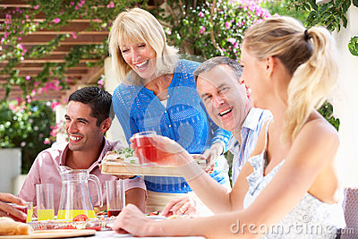 Young And Senior Couples Enjoying Family Meal