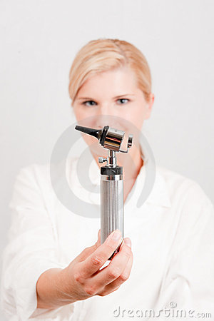 Young serious female doctor with medical tool