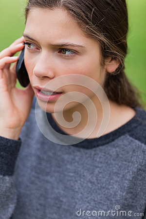 Young serious girl talking on the phone