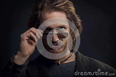 Young serious man with beard and moustache looking over his sunglasses