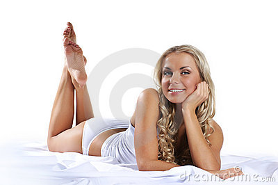 A young and sexy blond laying on a silk bed