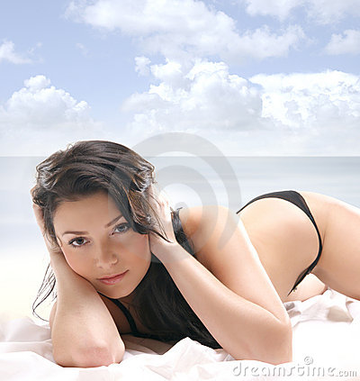 A young and sexy brunette is lying on a silk bed