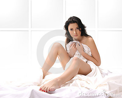 A young and sexy brunette sitting on a silk bed