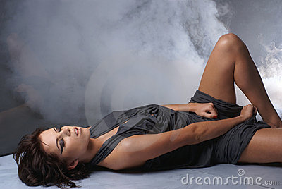 A young and sexy lady on a smoky background