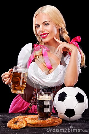 Free Young Sexy Oktoberfest Girl - Waitress, Wearing A Traditional Bavarian Dress, Serving Big Beer Mugs And Taking Soccer Stock Photo - 99609700