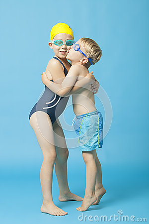 Young siblings in swimwear embracing and kissing over blue background