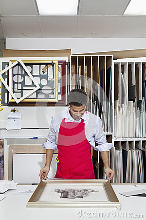Free Young Skilled Worker Adjusting Frame On Photograph Royalty Free Stock Image - 29670336