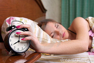 Young sleeping female turns alarm