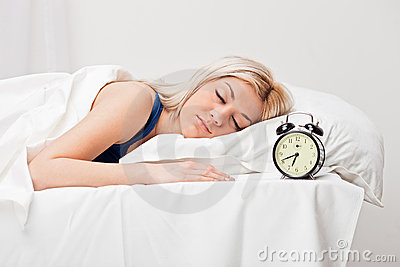 Young sleeping woman and alarm clock in bedroom