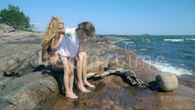 A young woman and her daughter are playing in rock pools among the coastal rocks on the beach. A young slender woman and her sweet daughter are playing in rock stock video
