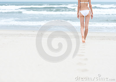 Slim girl in white swimsuit walking to ocean.