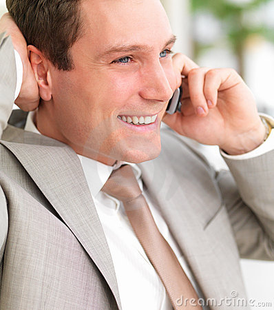Young smiling business man using cell phone with h