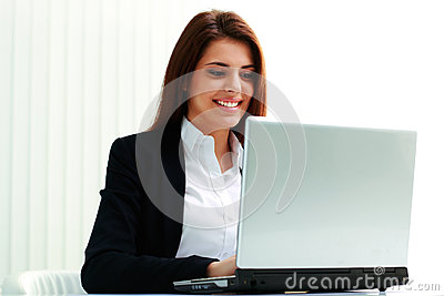 Young smiling businesswoman typing on the laptop