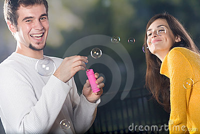 Young smiling couple blowing bubbles outdoors