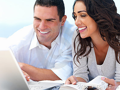 Young smiling couple looking at laptop