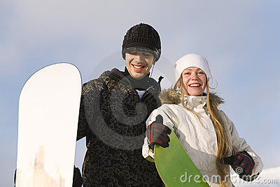Young smiling couple with snowboards