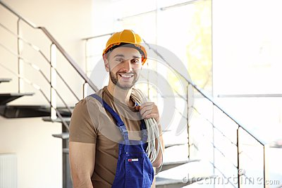 Young smiling electrician holding bunch of wires and standing Stock Photo