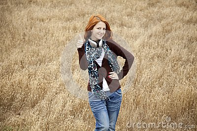 Young  smiling fashion with headphones at field.