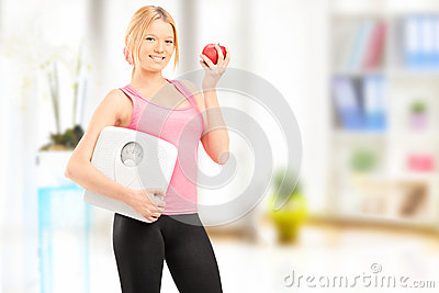 Young smiling female holding a weight scale and an apple, at hom