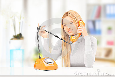 Young smiling female talking on a phone at home