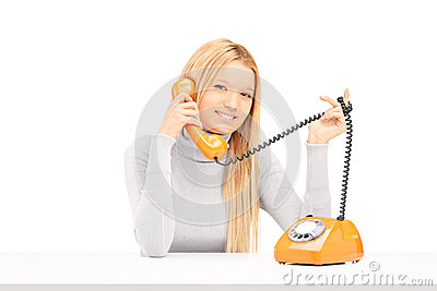 Young smiling female talking on a retro phone