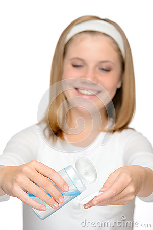 Young smiling girl applying face cleaning lotion