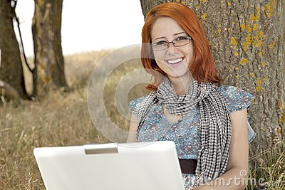 Young smiling girl in glasses and notebook