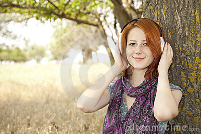 Young  smiling girl with headphones near tree.