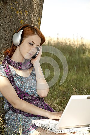Young smiling girl with notebook and headphones