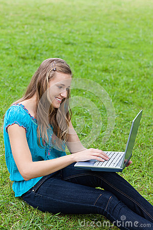 Young smiling girl typing on her laptop