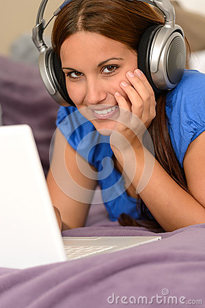 Young smiling girl using laptop with headphones