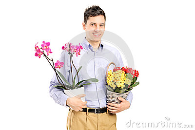 A young smiling male holding flowers