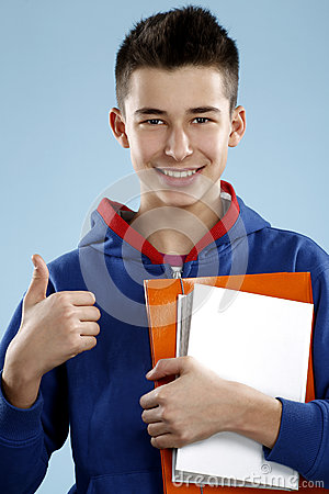 Young smiling male student teenager holding a book