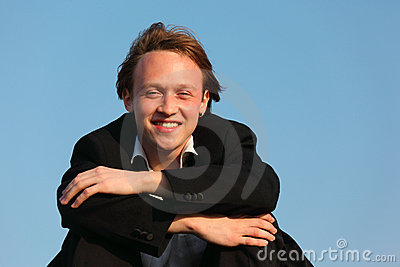 Young smiling man against sky