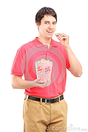 Young smiling man eating popcorn