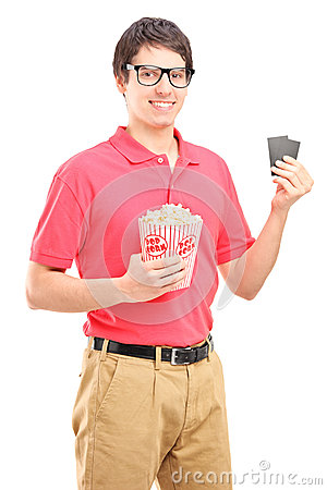 Young smiling man holding a popcorn box and two tickets for cinema
