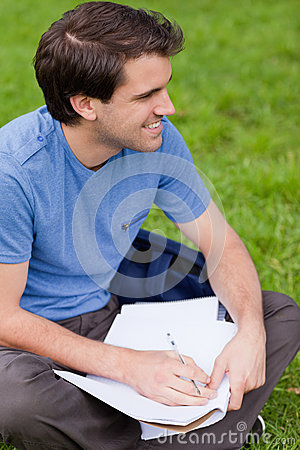 Young smiling man looking away while working on the grass