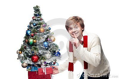 Young smiling man puts gift under christmas tree