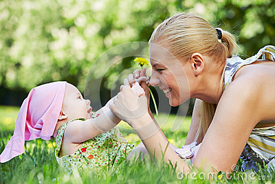 Young mother plays with her baby on grass