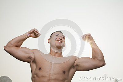Young, smiling, shirtless young man flexing his muscles with arms raised   outdoors in Beijing, China