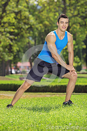 Young smiling sportsman exercising in a park