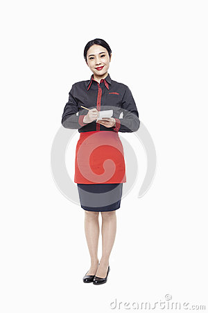 Young smiling waitress writing order on note pad, smiling, studio shot