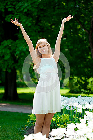 Young smiling woman with arms raised outdoors