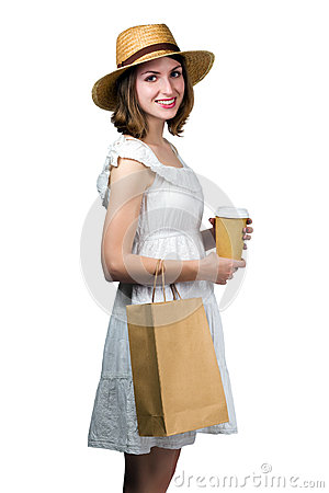 Young smiling woman holding a shopping bag and a paper cup