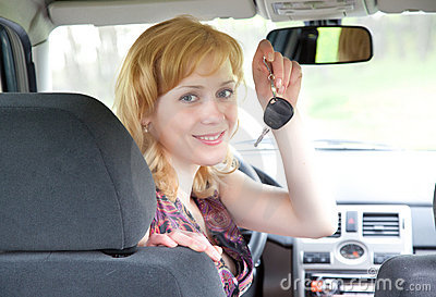 A young smiling woman with keys of car