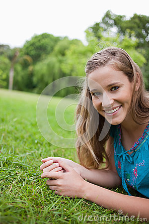 Young smiling woman lying on the grass in a park