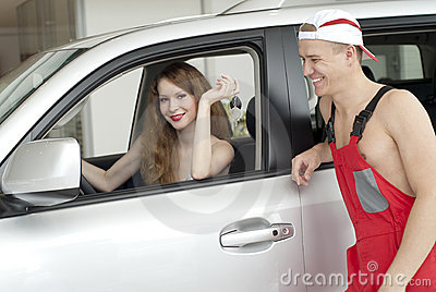 Young smiling woman and man near car
